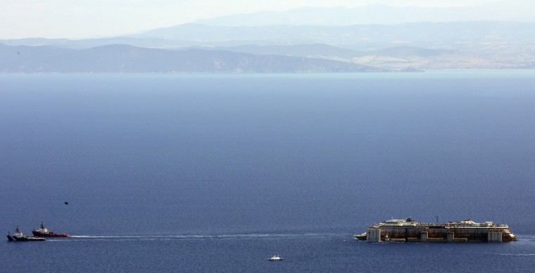 Tugboats drag cruise liner Costa Concordia after leaving Giglio Island July 23, 2014. The rusty hulk of the Costa Concordia cruise liner began its journey to the scrapyard on Wednesday after a two-year salvage operation off the Italian island where it capsized two years ago, killing 32 people. (Alessandro Bianchi/Reuters)