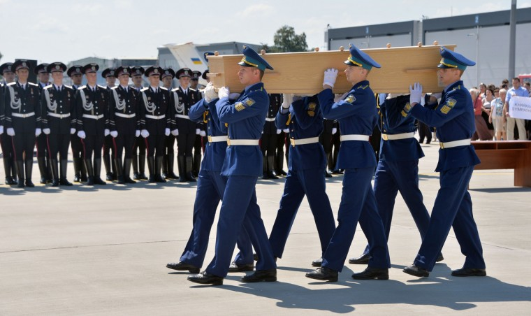Ukrainian soldiers carry a coffin with the remains of a victim of the Malaysia Airlines flight MH17 crash to a military plane during a ceremony at the airport of Kharkiv, Ukraine, on July 23, 2014. The first plane carrying bodies from downed Malaysia Airlines flight MH17 left eastern Ukraine for the Netherlands on July 23 following a sombre ceremony. The Dutch military aircraft took off from the airport in the government-controlled city of Kharkiv bound for Eindhoven after the first group of victims' remains were loaded onto the plane in wooden coffins. (Genya Savilov/AFP/Getty Images)