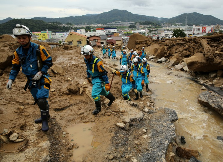 Members of Police arrive to doing rescue work in an area damaged by a landslide caused by torrential rain at the site of a landslide in a residential area in Hiroshima, Japan. At least 18 people were confirmed dead and several unaccounted people are missing after torrential rain caused flooding and landslides in the city of Hiroshima early today. (Buddhika Weerasinghe/Getty Images)