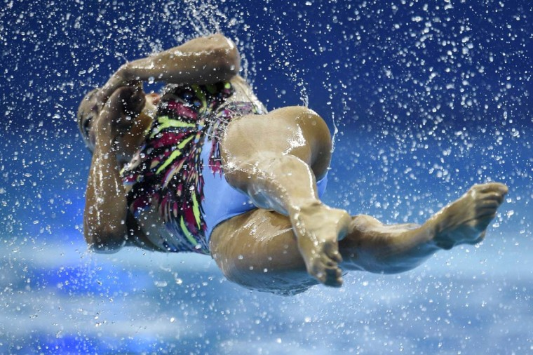 A member of Japan's team does a somersault as they compete in the team free routine final synchronised swimming event during the 2014 Asian Games at the Munhak Park Tae-hwan Aquatics Center in Incheon on September 22, 2014. (Martin Bureau/AFP/Getty Images)