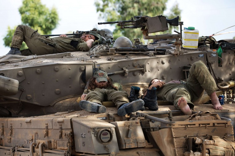Israeli soldiers rest on Merkava tanks at an army deployment near the Israeli-Gaza border. Israeli strikes killed 20 people in Gaza on July 19, 2014, taking the death toll from a 12-day bombardment to 318, as UN chief Ban Ki-moon headed to the region to join truce efforts. (MenahemKahana/AFP-Getty Images)